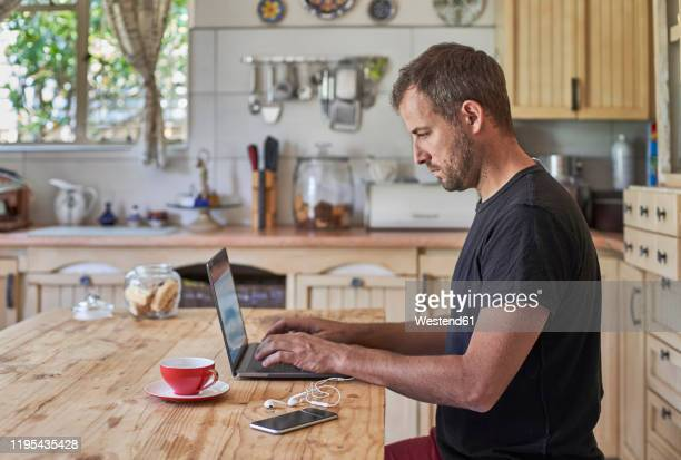 man working from home, sitting at kitchen table, using laptop and smartphone - mid adult men stock pictures, royalty-free photos & images