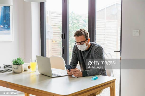 man working from home. using smartphone - pandemic illness stock pictures, royalty-free photos & images