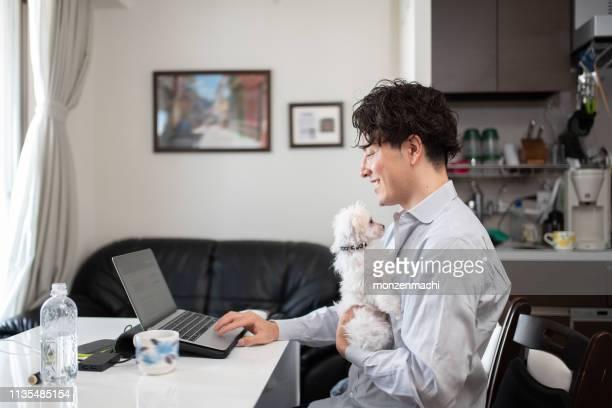 ペットと一緒に家で働く男 - テレワーク ストックフォトと画像
