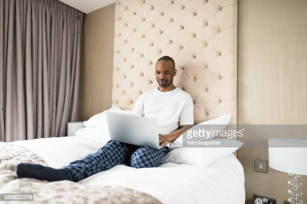 man working from the bedroom hotel