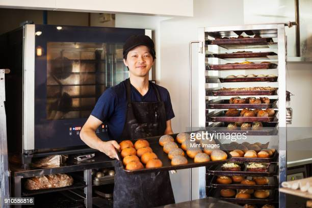man working in a bakery, holding large tray with freshly baked rolls, smiling at camera. - catering building stock pictures, royalty-free photos & images