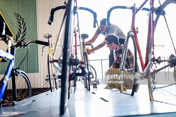 A man working in a bicycle repair shop, checking a bike with a customer.