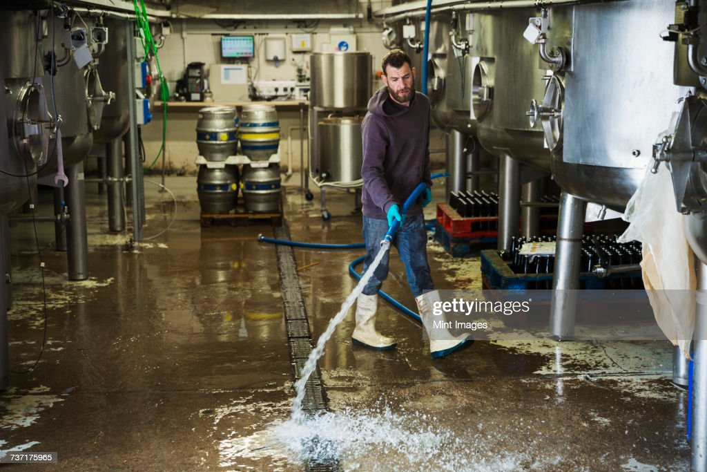 Man working in a brewery, cleaning floor with water hose. : Stock Photo