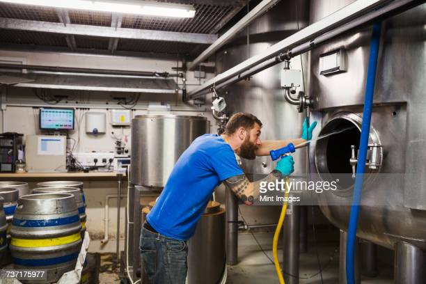 Man working in a brewery, cleaning inside of a large stainless steel kettle with a high pressure washer.