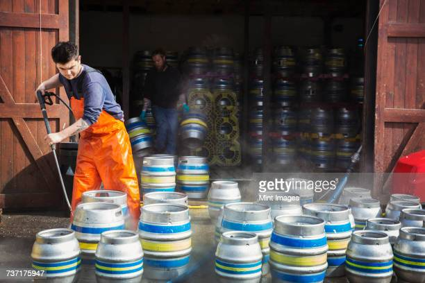 man working in a brewery, cleaning metal beer kegs with a high pressure washer. - industrial hose stock pictures, royalty-free photos & images