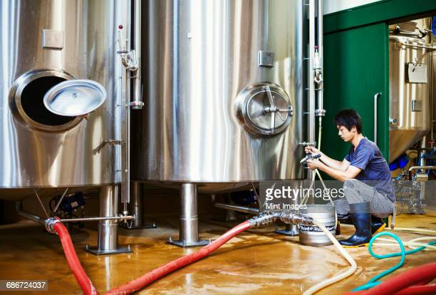 Man working in a brewery, kneeling beside a metal beer tank.