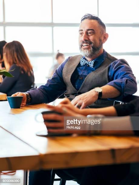 man aan het werk in de vergaderruimte van een cafe coffee shop - strikje stockfoto's en -beelden