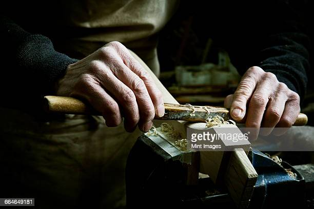 A man working in a furniture makers workshop, using a rasp on a piece of wood in a clamp.