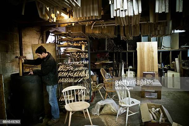A man working in a furniture makers workshop. Windsor chairs.