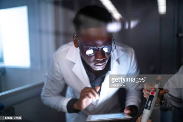 man working in a laboratory, using digital tablet - laboratory glassware stock pictures, royalty-free photos & images