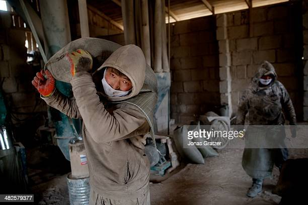 Man working in a mine carries bags filled with stones on the outskirts of the Sharyngol district in Mongolia where virtually everyone in the city...