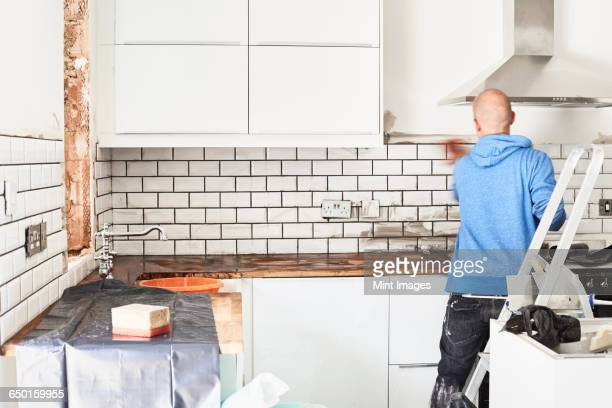 A man working in a new kitchen, a tiler applying tiles to the wall behind the cooker.