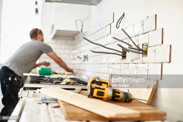 a man working in a new kitchen, a tiler applying tiles to the wall behind the cooker.  - home improvement stock pictures, royalty-free photos & images