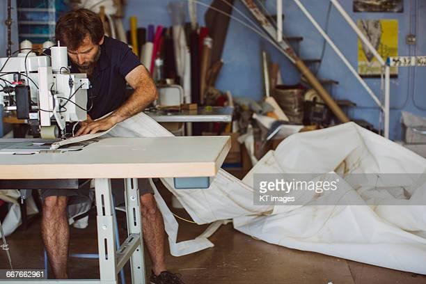 Man working in a sail making workshop