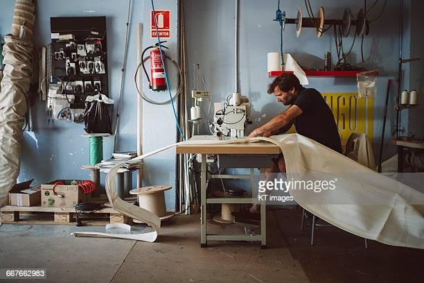 man working in a sail making workshop - sewing stock pictures, royalty-free photos & images