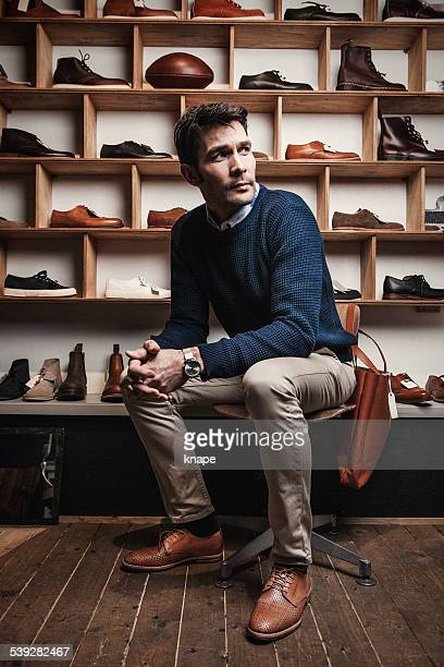man working in a small business retailer at shoe store - work shoe stock photos and pictures