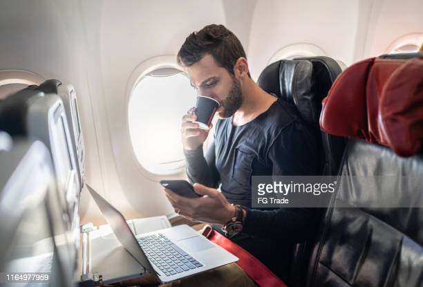 man working in airplane using cellphone and drinking coffee - pardo brazilian stock pictures, royalty-free photos & images