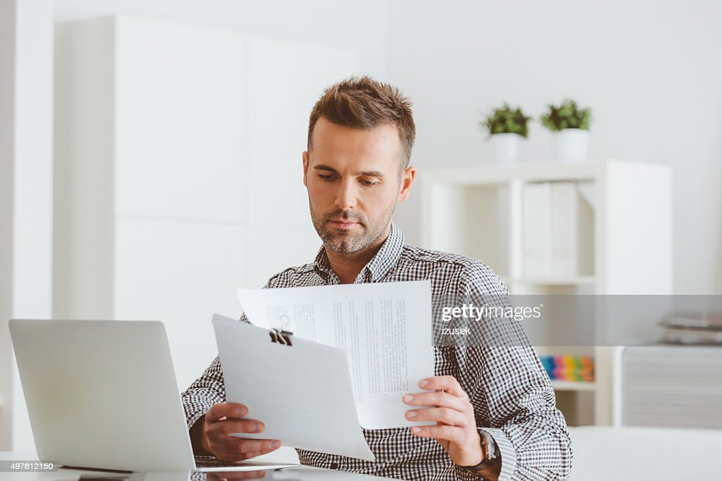 Man working in an home office, reading documents : Stock Photo