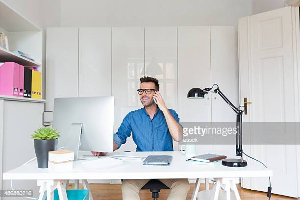 Man working in an office, talking on smart phone