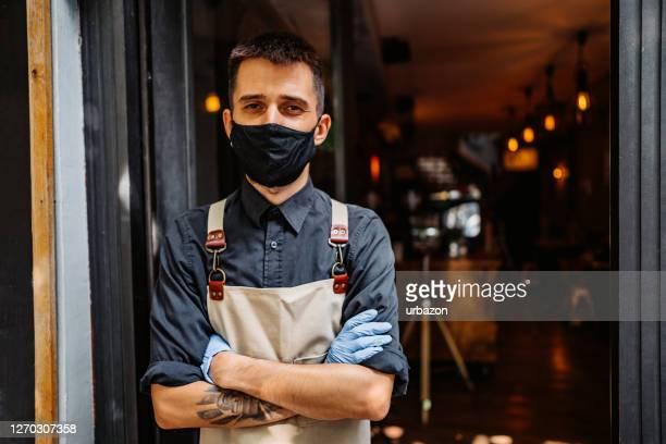 mens die in café, met gezichtsmasker werkt - beschermend masker werkkleding stockfoto's en -beelden