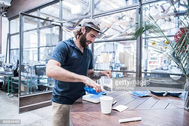 Man working in coffee roasting warehouse holding fresh coffee beans