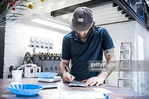 Man working in coffee roasting warehouse, writing in notebook