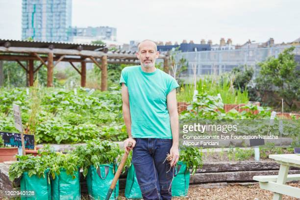 man working in community garden - compassionate eye foundation stock pictures, royalty-free photos & images