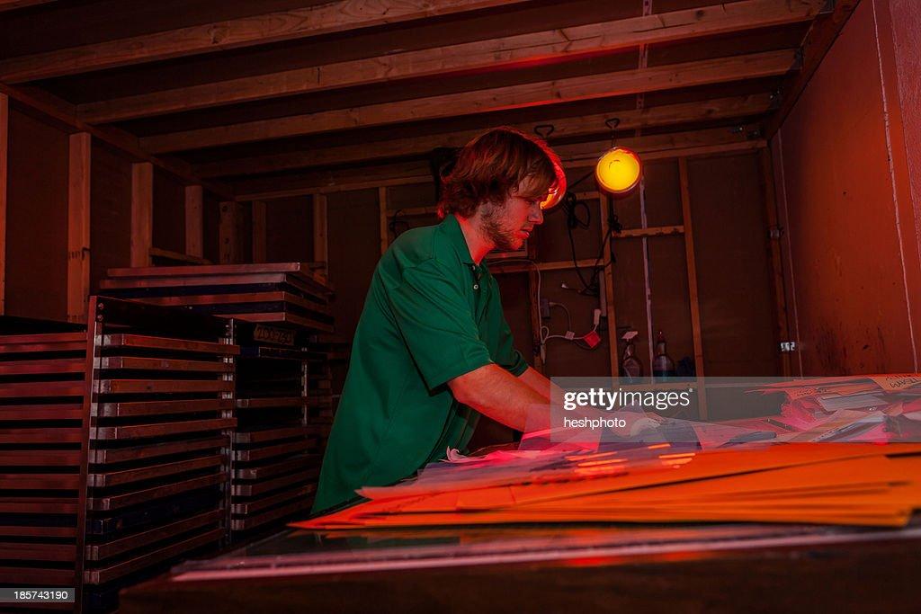 Man working in darkroom in screen printing workshop : Stock Photo
