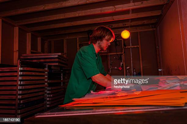 Man working in darkroom in screen printing workshop