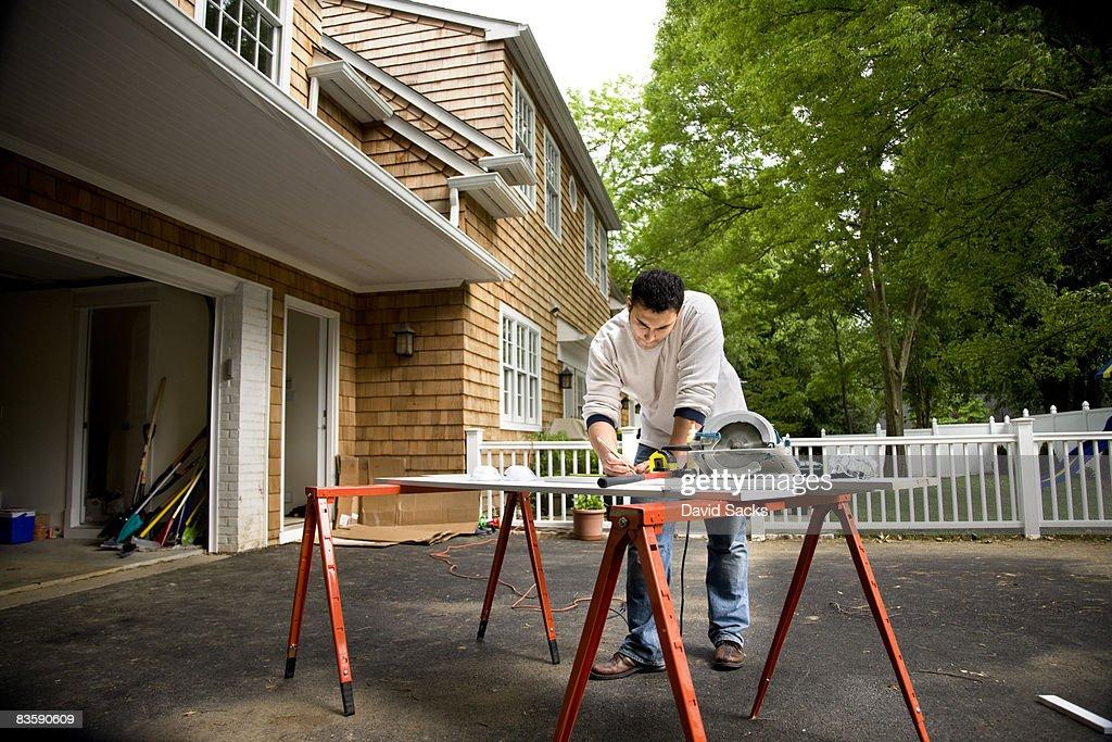 Man working in driveway : Stock Photo