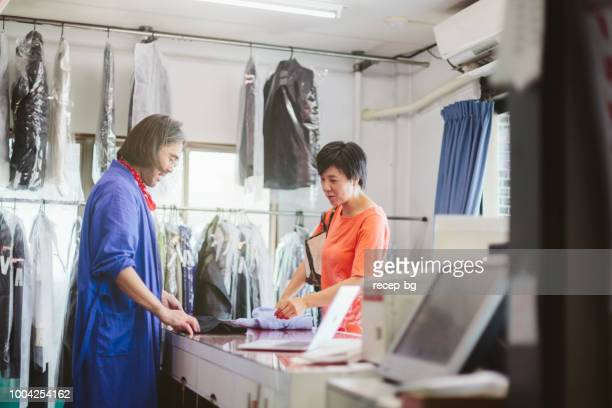 man working in dry cleaning shop - dry cleaner stock pictures, royalty-free photos & images