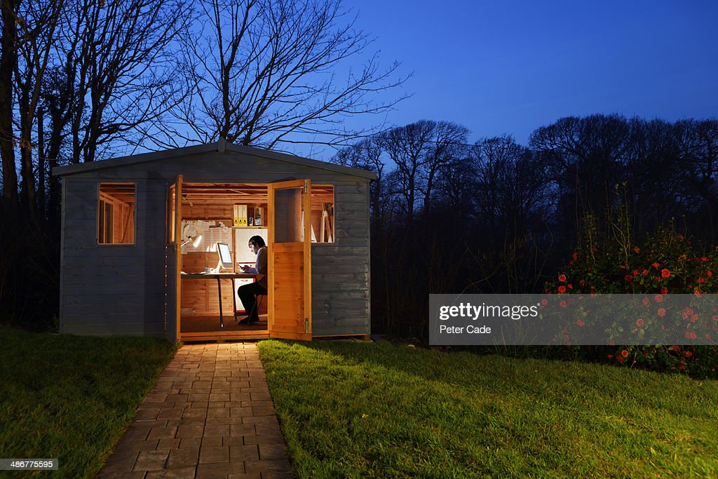 Man working in garden shed at night : ストックフォト