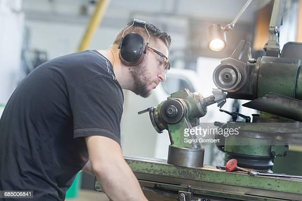 man working in grinding workshop - sigrid gombert stock-fotos und bilder