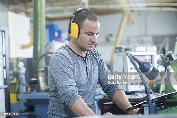 man working in grinding workshop - sigrid gombert stock pictures, royalty-free photos & images