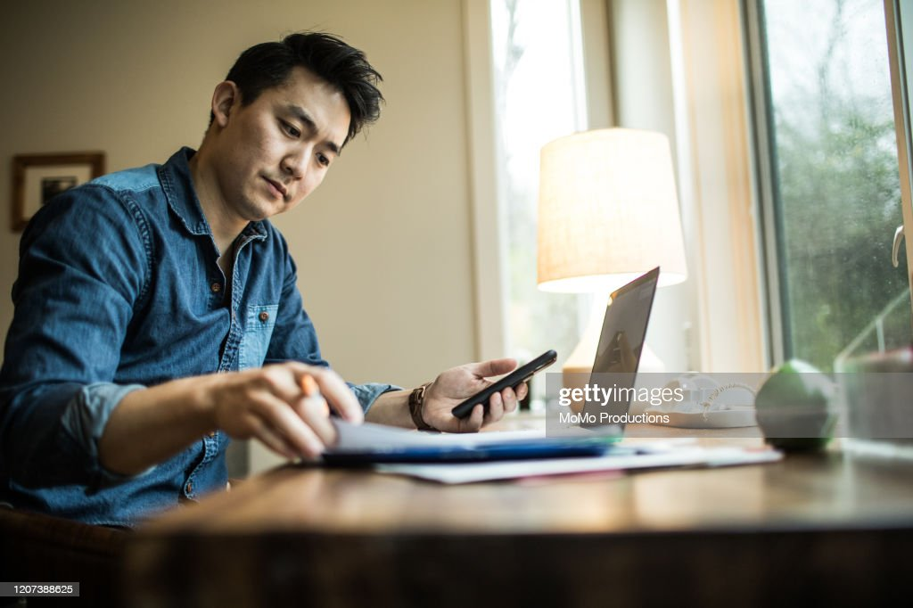 Man (early 30s) working in home office : Stock Photo