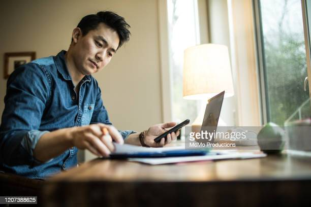 man (early 30s) working in home office - finance stock pictures, royalty-free photos & images