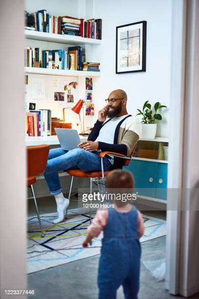 man working in home office with daughter in doorway - man made object stock pictures, royalty-free photos & images