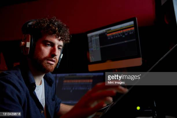 man working in music studio using computer wearing head phones - the media stock pictures, royalty-free photos & images