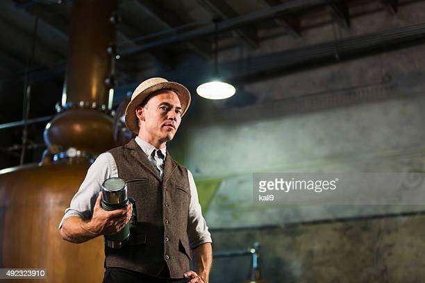 Mann arbeitet in der alten Destillerie mit Kaffeepause