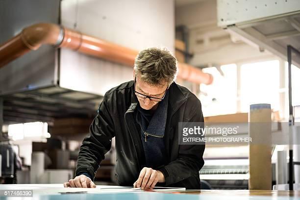 Hombre trabajando en la fábrica de la impresión