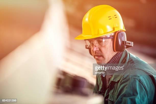 Mann arbeitet im Sägewerk