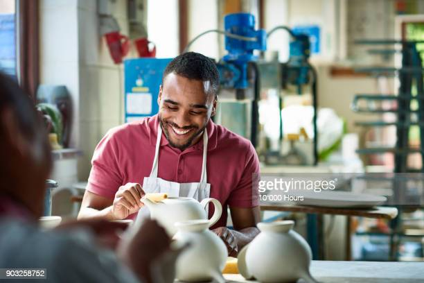 man working in small pottery factory - hobbies stock pictures, royalty-free photos & images