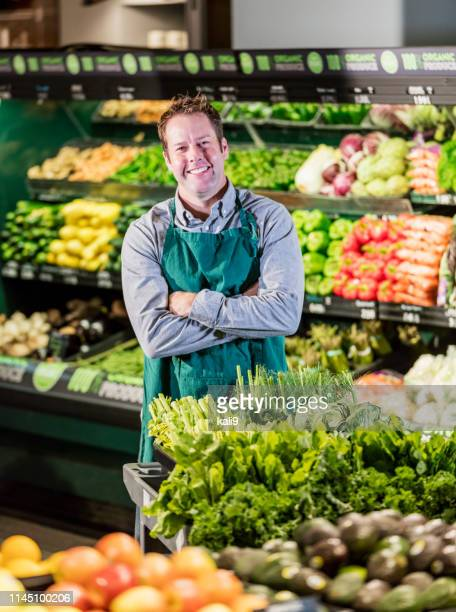 man working in supermarket produce aisle - produce aisle stock pictures, royalty-free photos & images