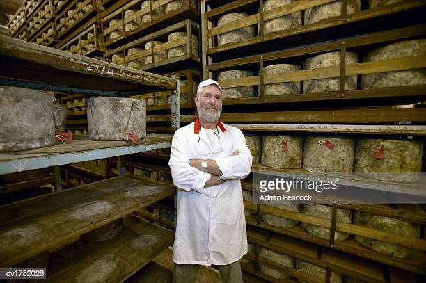Man Working in the Cheesemaking Industry Standing Beside Shelves of Cheese