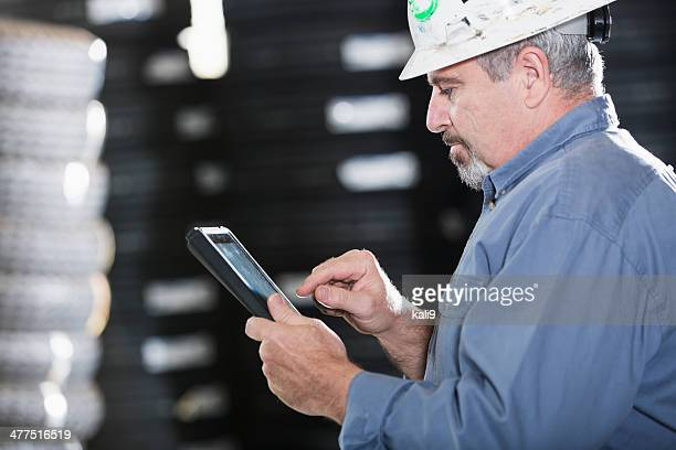Man working in warehouse using digital tablet