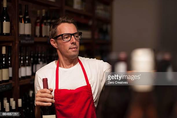 Man working in wine shop holding bottles of wine