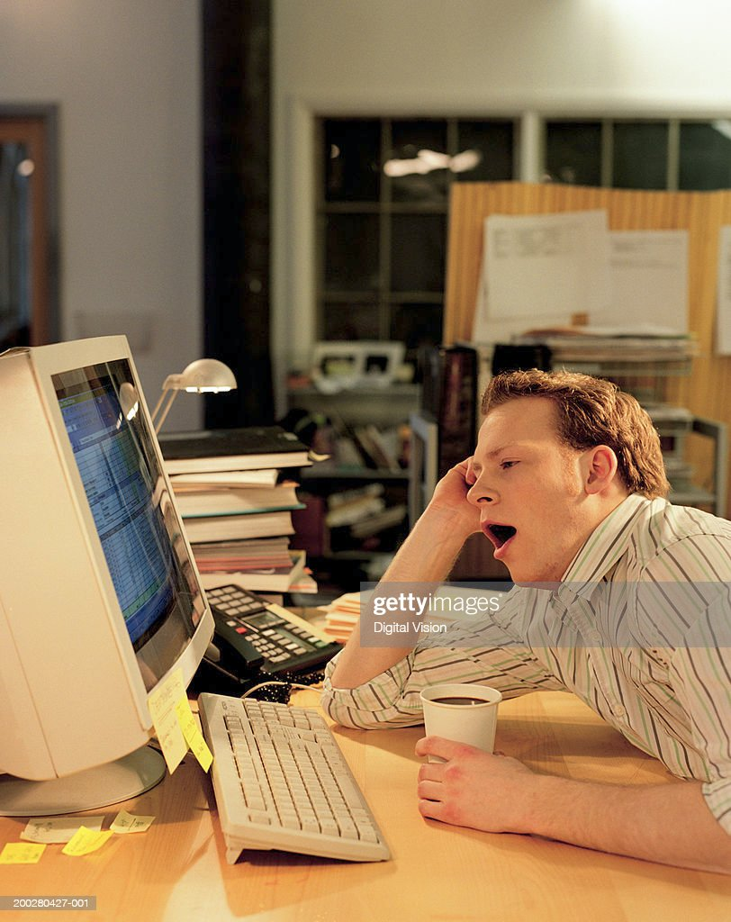 Man working late at computer holding cup of coffee, yawning : Stock Photo