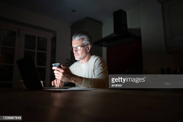 man working late from home and multi-tasking using technology - stream stock pictures, royalty-free photos & images