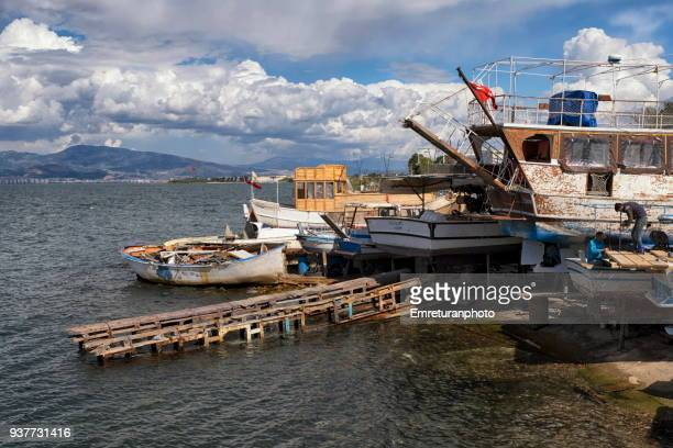 man working on a boat in small shipyard at narlieder,izmir. - emreturanphoto stock pictures, royalty-free photos & images