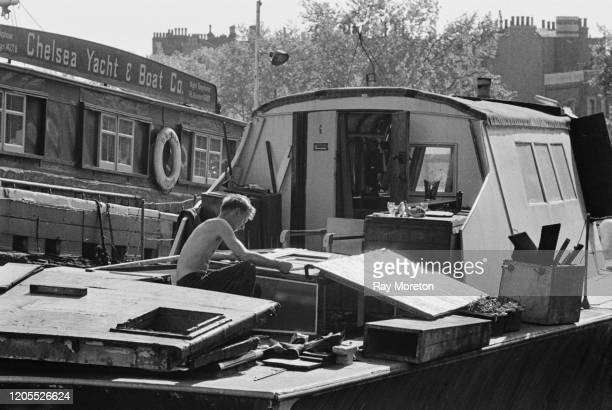 A man working on a boat moored on the Thames at Chelsea London September 1959